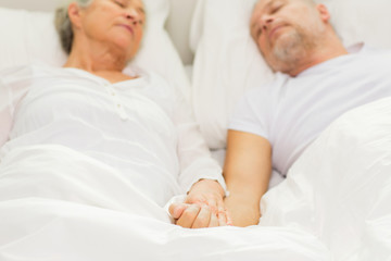 close up of senior couple sleeping in bad at home