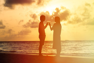Silhouette of couple drinking wine at sunset