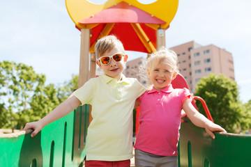 two happy kids hugging on children playground