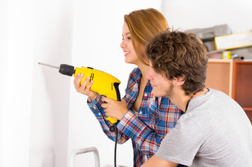 Couple renovating together as woman using power drill on wall with man standing next to her observing