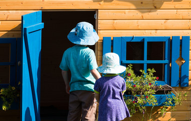 girl and boy standing infront of the wooden playhouse with blue windows