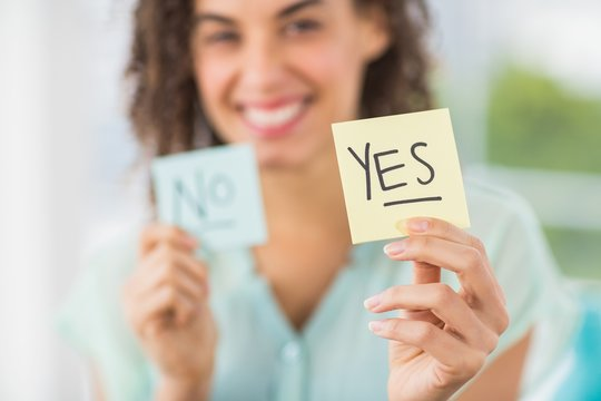 Smiling businesswoman holding yes and no sticks