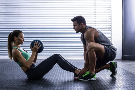Muscular couple doing abdominal ball exercise