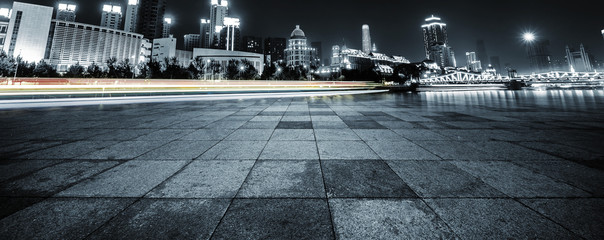 light trails and cityscape with empty road floor Fotomurales