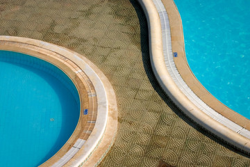 Swimming pools. An aerial view of a pair of ornate hotel outdoor swimming pools reflecting the hot North African sun in Tunisia.