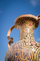 Tunisian Urn. A low angle detail view of a painted Tunisian urn offset against a blue cloudless sky providing copy space.