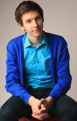 the young man in a blue jumper and a blue shirt looks at the viewer