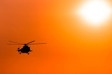 transport helicopter silhouette against a red sky