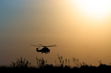 silhouette of military helicopter above the ground