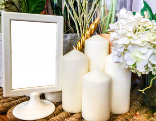 Blank White Frame on Wooden Table with Candle and Flowers used as Template