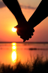 silhouette of couple at sunset holding hands