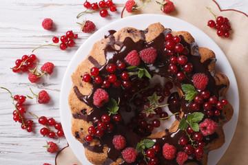 berry sponge cake with chocolate on a plate closeup. Horizontal top view