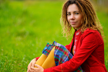 Girl with dreadlocks sits on grass