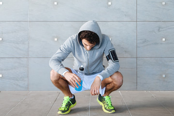 A young man in sportswear resting in the shade of a building in a summer day, drinking an energy drink blue color from a bottle before resuming training