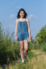 Lovely young brunette girl with a bouquet of wild flowers is on the field road summer