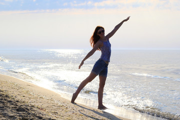 young slender woman doing gymnastics on the beach