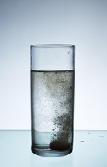 Glass with efervescent tablet in water.
