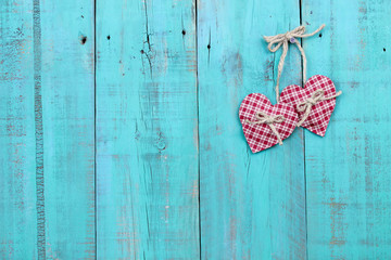 Red hearts hanging on antique rustic teal blue wood background