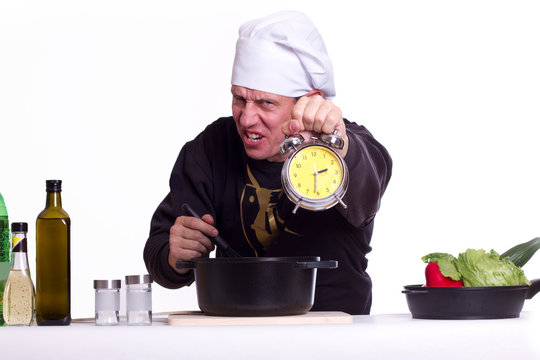 Koch hält genervt die Uhr hoch