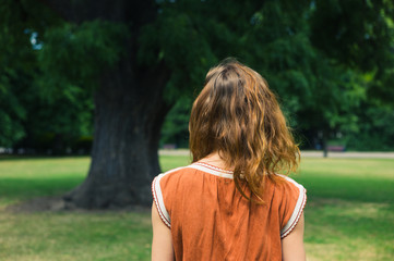 Young woman looking at tree in park