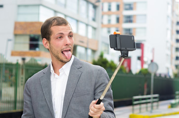 Man formal clothing posing with selfie stick in urban
