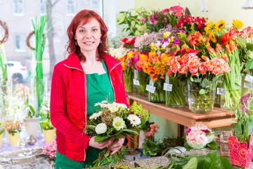 Florist binding flower bunch in shop