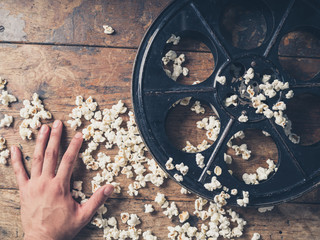 Hand with film reel and popcorn