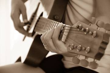 Woman playing acoustic guitar, sepia tone