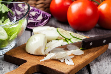 Chopped vegetables: onion and cucumber on cutting board