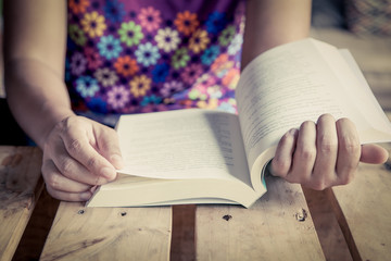 Woman hand holding book to read in library