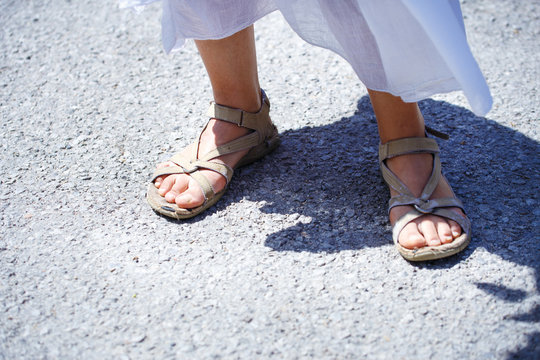 woman stands in sandals on the road, detail