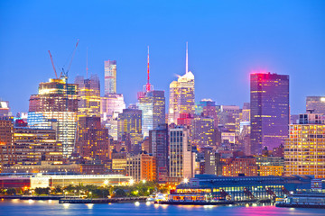 New York City skyline, modern illuminated colorful buildings in downtown Manhattan at sunset