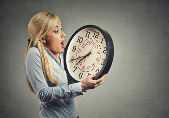 woman holding clock looking anxiously, running out of time