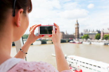 Woman taking pictures of Big Ben, London UK with smartphone, mobile.