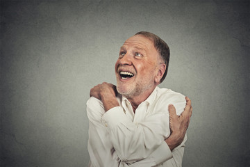 smiling man holding hugging himself