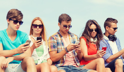 group of friends with smartphones outdoors