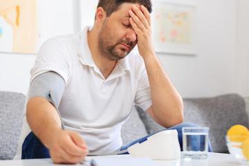 Man measuring  his blood pressure feeling sick.