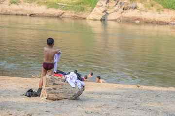 Boy wearing white shirt  after swimming in river with his friend