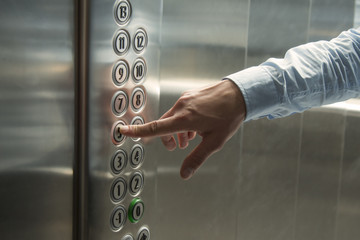 Finger pressing the button in the elevator
