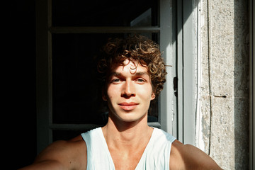 Top view of handsome young curly man making selfie and smiling w