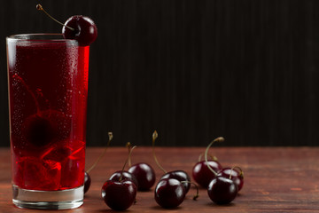 juice cherry with ripe berries on wooden background. A healthy diet