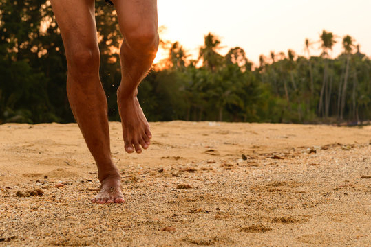 Barefoot running on beach at sunset.