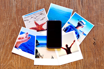 smartphone and some photos on a wooden surface