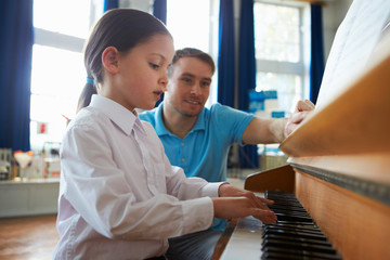 Female Student Enjoying Piano Lesson With Teacher