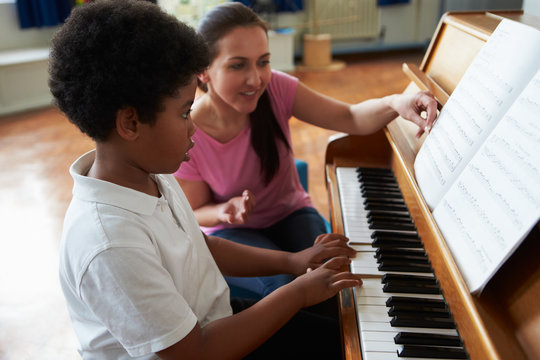 Male Student Enjoying Piano Lesson With Teacher