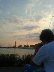 Ragazzo che fotografa il tramonto nel porto