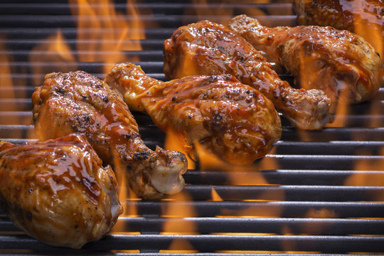 Chicken legs grilling over flames on a barbecue