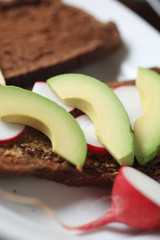 Avocado and radish slices on dark bread spread with whole grain mustard