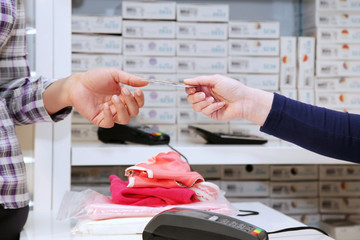 Hands of client and the seller in shop
