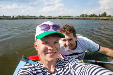 Young people make selfie during kayaking on a river in beautiful nature